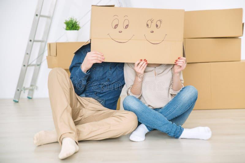 Coppie allegre che si nascondono sotto la scatola fotografie stock libere da diritti