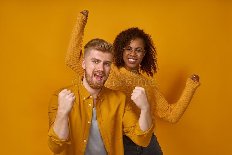 Coppie allegre che stringono i pugni come vincitori o felici di raggiungere l'obiettivo fotografia stock
