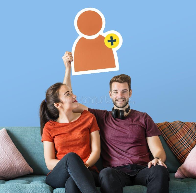 Coppie allegre che tengono un'icona di richiesta dell'amico fotografia stock