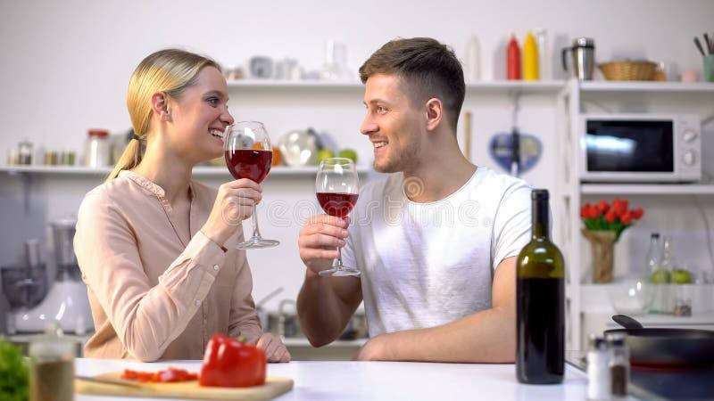 Coppie allegre con i vetri di vino che spendono insieme tempo alla cucina, romanzesca fotografie stock