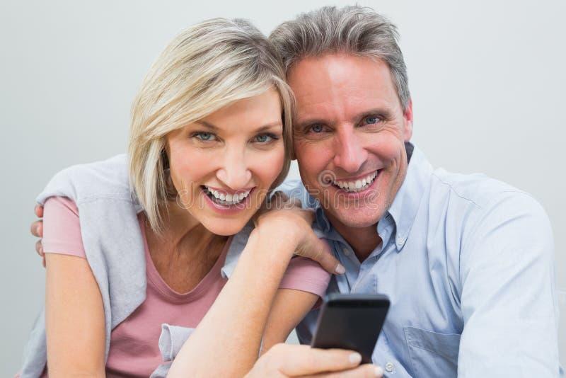 Coppie allegre con il telefono cellulare fotografie stock libere da diritti