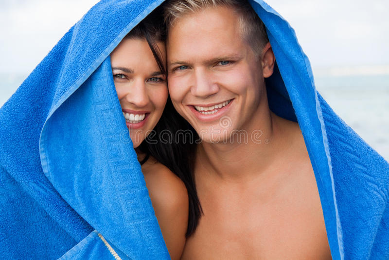 Coppie allegre con un asciugamano che riguarda le loro teste fotografia stock libera da diritti