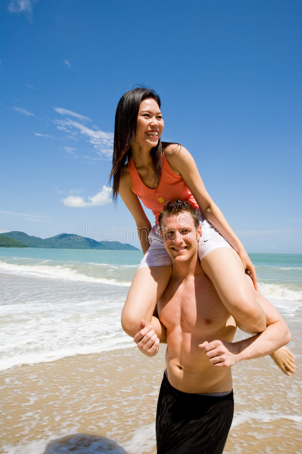 Coppie allegre dalla spiaggia immagine stock
