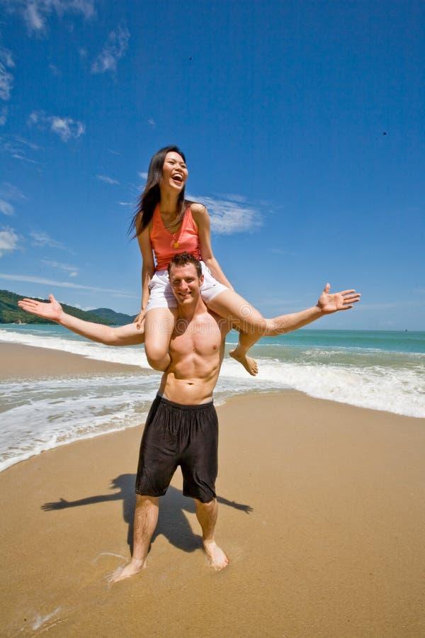 Coppie allegre dalla spiaggia fotografia stock
