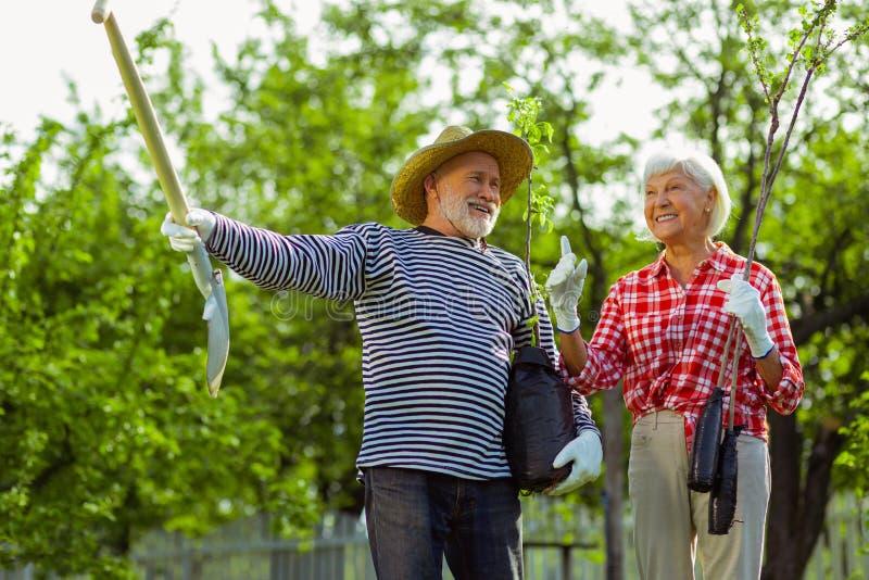 Coppie allegre del marito pensionato e della moglie che parlano prima della piantatura degli alberi fotografia stock