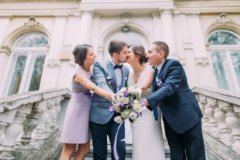 Coppie allegre della persona appena sposata con il groomsman felice e la damigella d'onore che posano alle scale di costruzione c immagine stock libera da diritti
