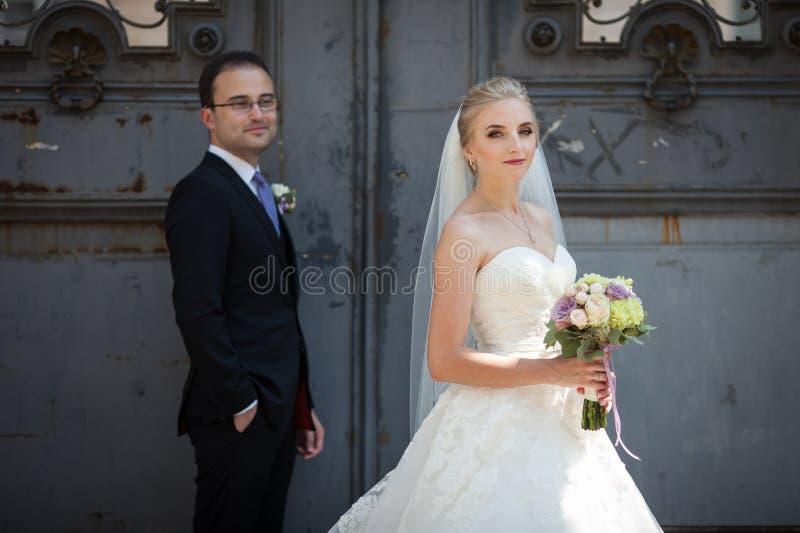 Coppie allegre e romantiche delle persone appena sposate che posano vicino al vecchio portone fotografia stock