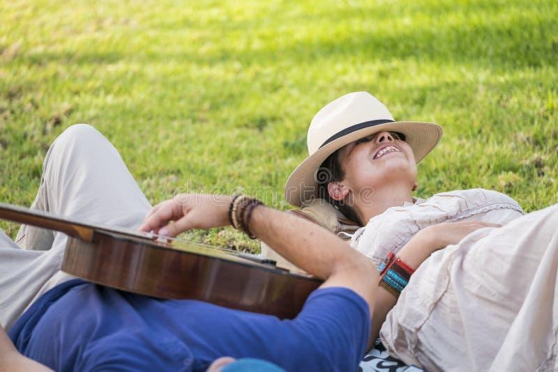 Coppie allegre felici e rilassate che indicano sull'erba naturale e godere dell'attività di svago all'aperto con un buon tempo de fotografia stock libera da diritti
