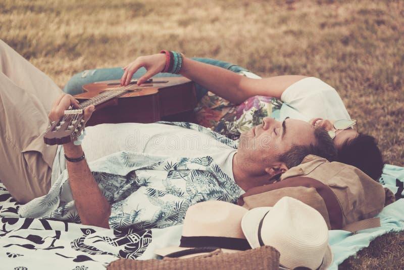 Coppie allegre felici e rilassate che indicano sull'erba naturale e godere dell'attivit? di svago all'aperto con un buon tempo de fotografia stock libera da diritti