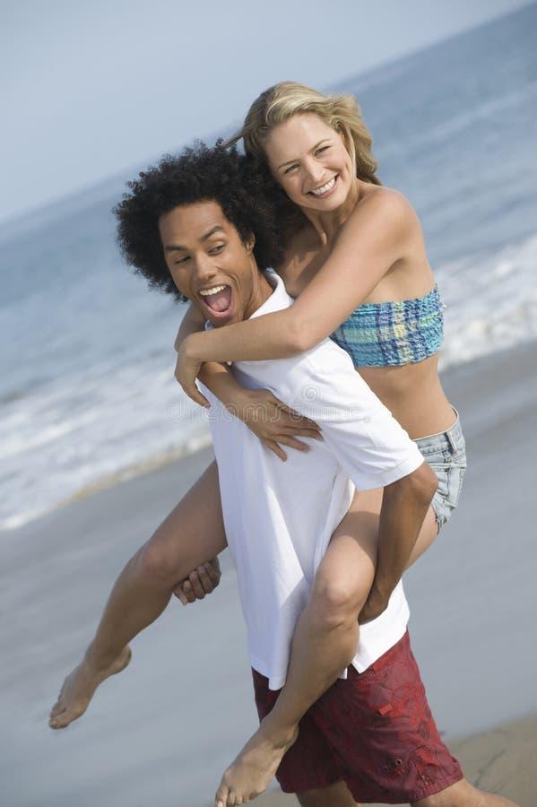 Coppie allegre sulla spiaggia fotografie stock