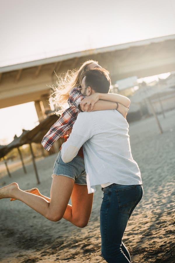 Coppie allegre vero felici divertendosi alla spiaggia fotografia stock