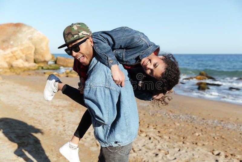 Coppie amorose africane sorridenti che camminano all'aperto alla spiaggia fotografia stock libera da diritti