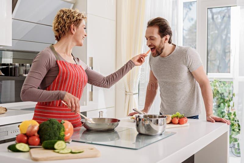 Coppie amorose allegre che mangiano verdura durante la cottura immagini stock libere da diritti