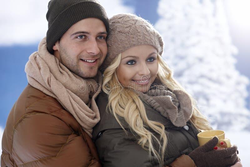 Coppie amorose che abbracciano all'orario invernale immagini stock