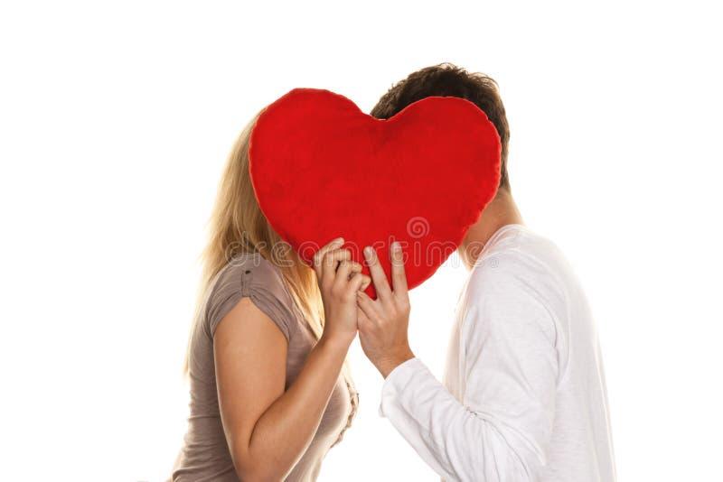 Coppie amorose che baciano dietro un cuore. L'amore è Sho fotografia stock