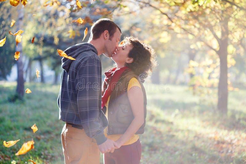 Coppie amorose che baciano nel parco alla luce solare sul backg degli alberi fotografie stock