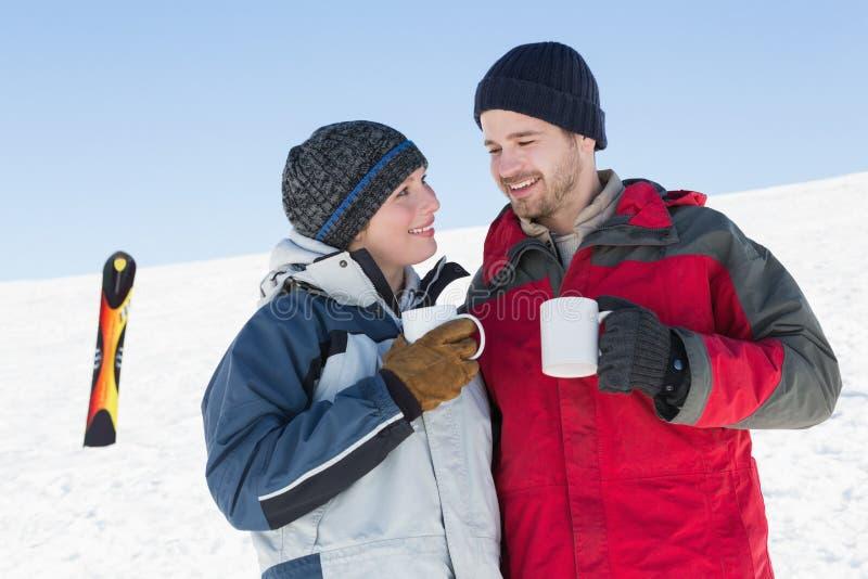 Coppie amorose che mangiano caffè con il bordo dello sci in neve fotografia stock