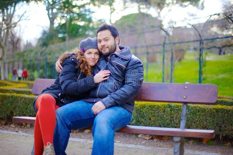Coppie amorose che si siedono su un banco di parco immagine stock libera da diritti