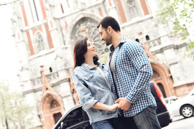 Coppie amorose che si tengono per mano su un fondo della chiesa fotografia stock libera da diritti