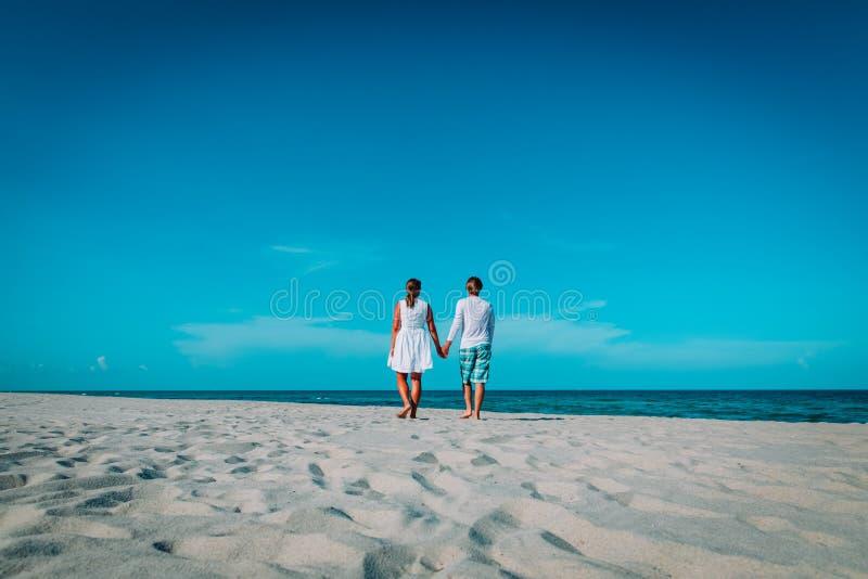 Coppie amorose felici che camminano sulla spiaggia tropicale fotografia stock