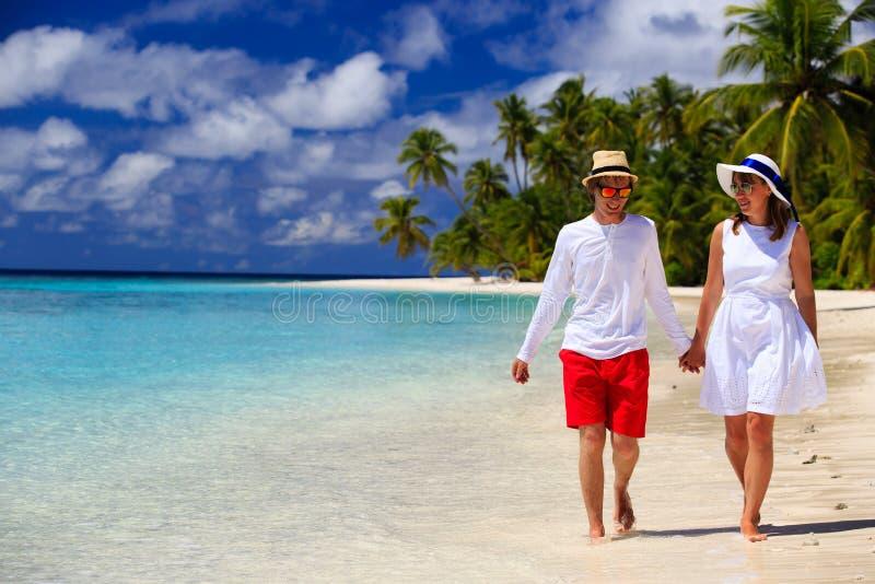 Coppie amorose felici che camminano sulla spiaggia tropicale immagine stock libera da diritti