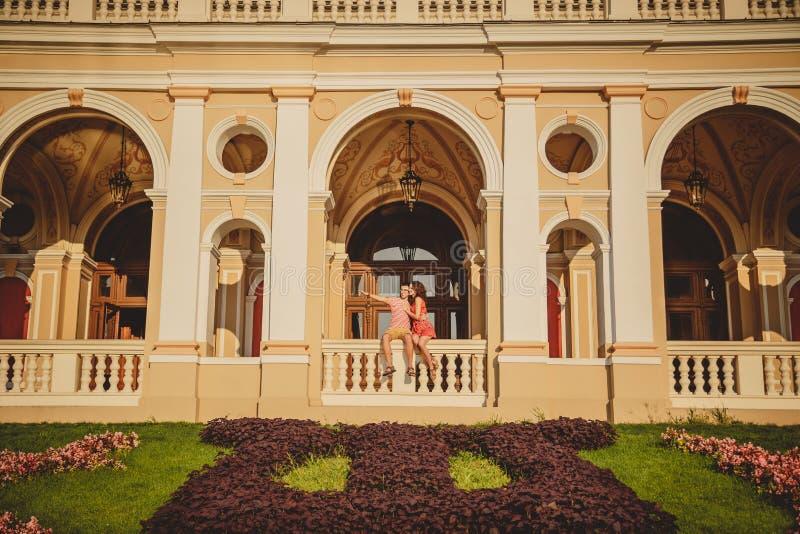 Coppie amorose felici che si siedono fuori al balcone di Odessa Opera House L'uomo sta indicando con il suo dito a qualcosa immagini stock libere da diritti