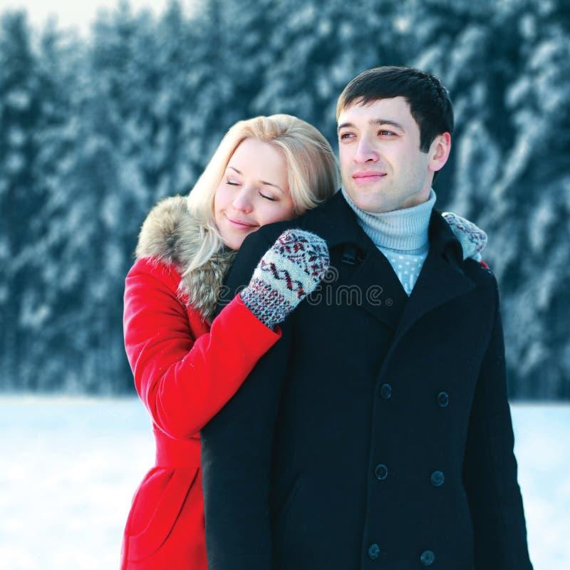 Coppie amorose felici del ritratto giovani che abbracciano nel giorno di inverno sopra la foresta nevosa degli alberi immagini stock