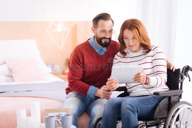 Coppie amorose felici facendo uso di una compressa immagine stock
