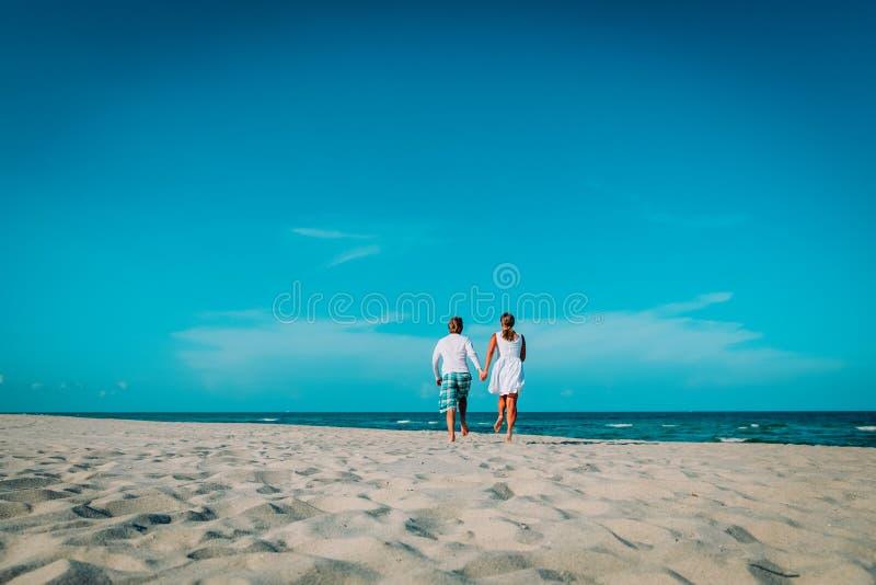 Coppie amorose felici funzionate per godere della spiaggia tropicale immagini stock libere da diritti