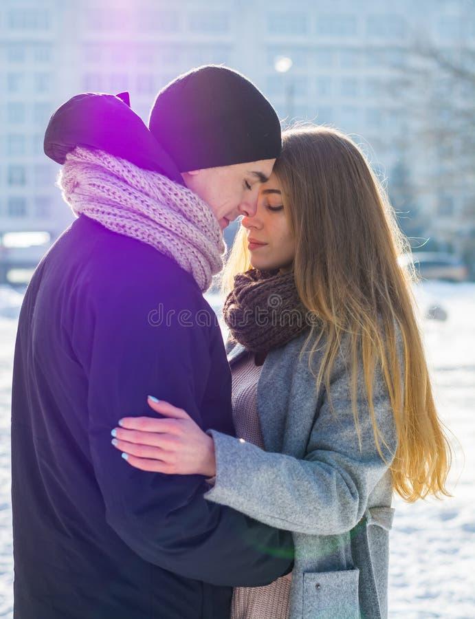 Coppie amorose in inverno Il tipo abbraccia una ragazza sulla via nell'inverno immagine stock