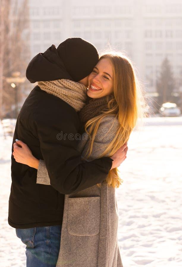 Coppie amorose in inverno Il tipo abbraccia una ragazza sulla via nell'inverno immagine stock libera da diritti