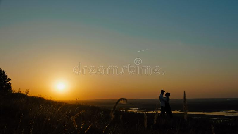 Coppie amorose - sfidi il giovane e la bella ragazza alla siluetta del tramonto, grandangolare fotografia stock