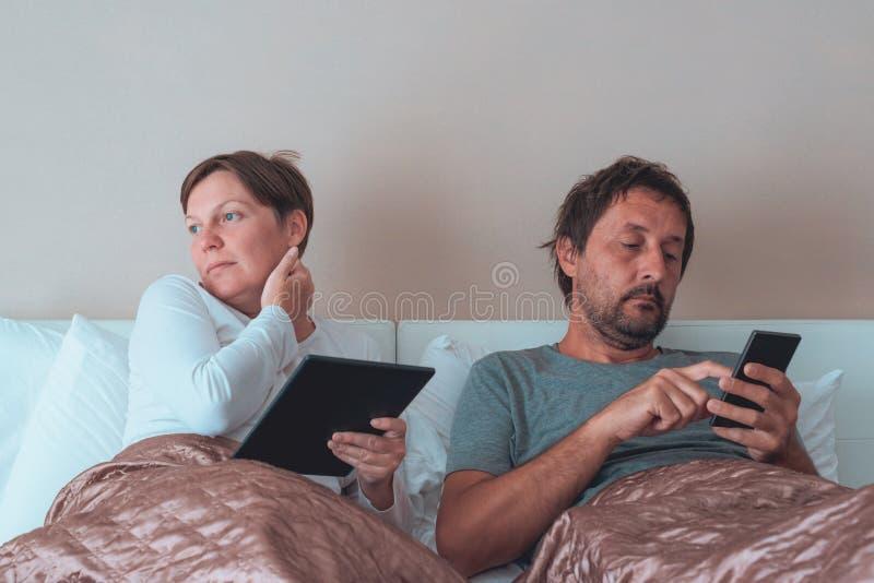 Coppie annoiate, marito e moglie in camera da letto fotografie stock libere da diritti