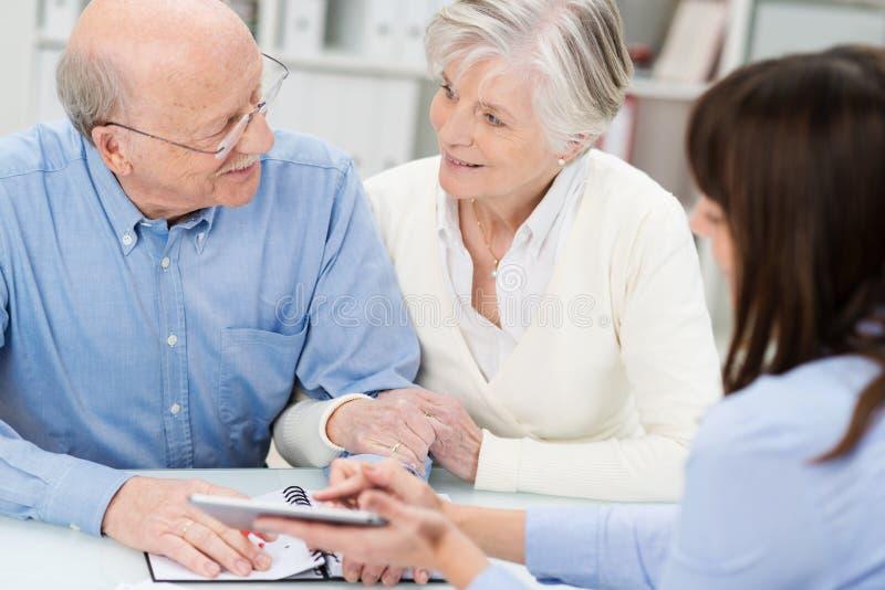 Coppie anziane affettuose in una riunione d'affari immagini stock libere da diritti