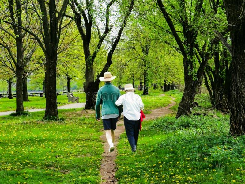 Coppie anziane che camminano attraverso il parco fotografia stock
