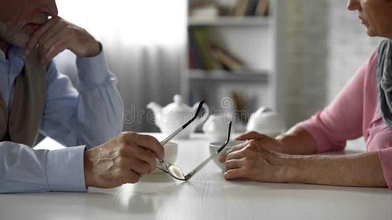 Coppie anziane che discutono problema che si siede attraverso la tavola sopra la tazza di tè, disputa immagine stock