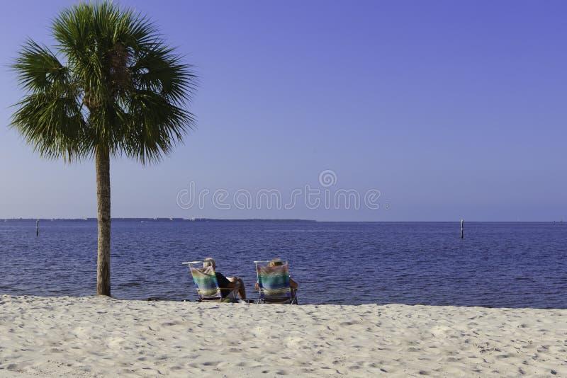 Coppie anziane che si distendono sulla spiaggia fotografie stock libere da diritti