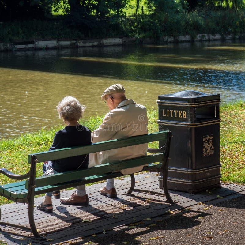 Coppie anziane che si siedono sul banco fotografia stock libera da diritti