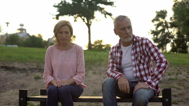 Coppie anziane che si siedono sul banco, uomo triste che pensa ai problemi della famiglia, litigio immagini stock