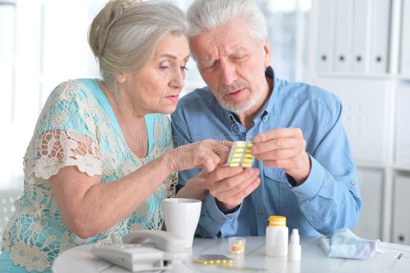 Coppie anziane con le pillole fotografia stock libera da diritti