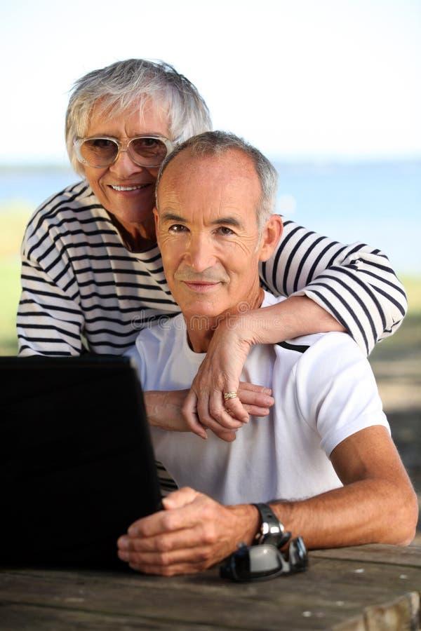 Coppie anziane con un computer fotografia stock