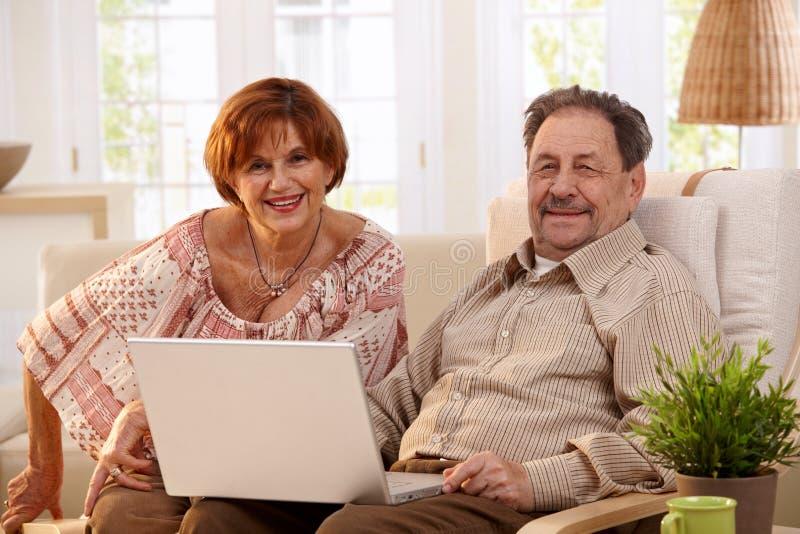 Coppie anziane facendo uso del computer portatile immagine stock libera da diritti