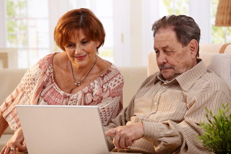 Coppie anziane facendo uso di elaboratore-elaboratore fotografia stock