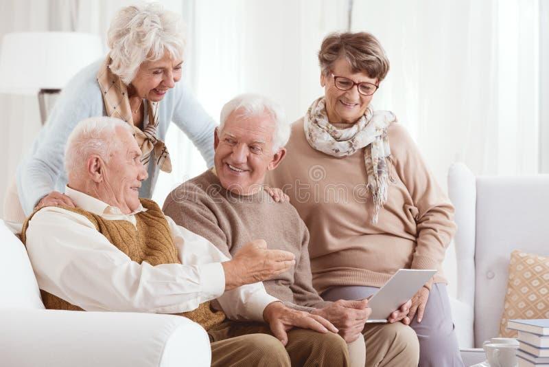 Coppie anziane facendo uso di tecnologia fotografia stock