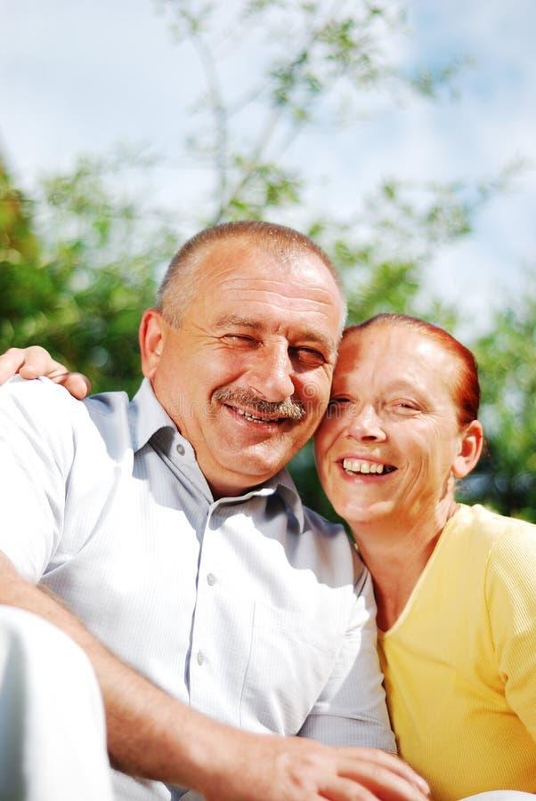 Coppie anziane felici che si abbracciano esterno fotografia stock