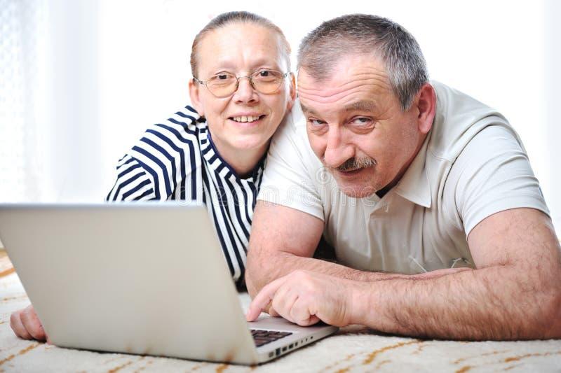 Coppie anziane positive con il computer portatile fotografia stock