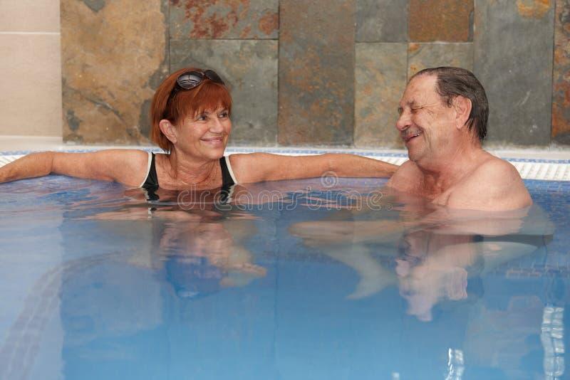 Coppie anziane a sorridere del raggruppamento dell'acqua calda immagine stock libera da diritti
