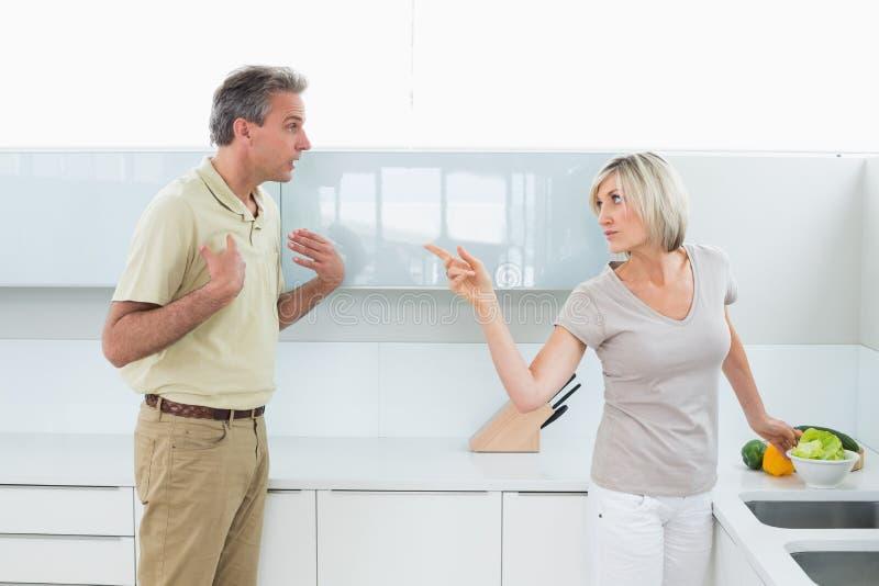 Coppie arrabbiate che discutono nella cucina immagine stock