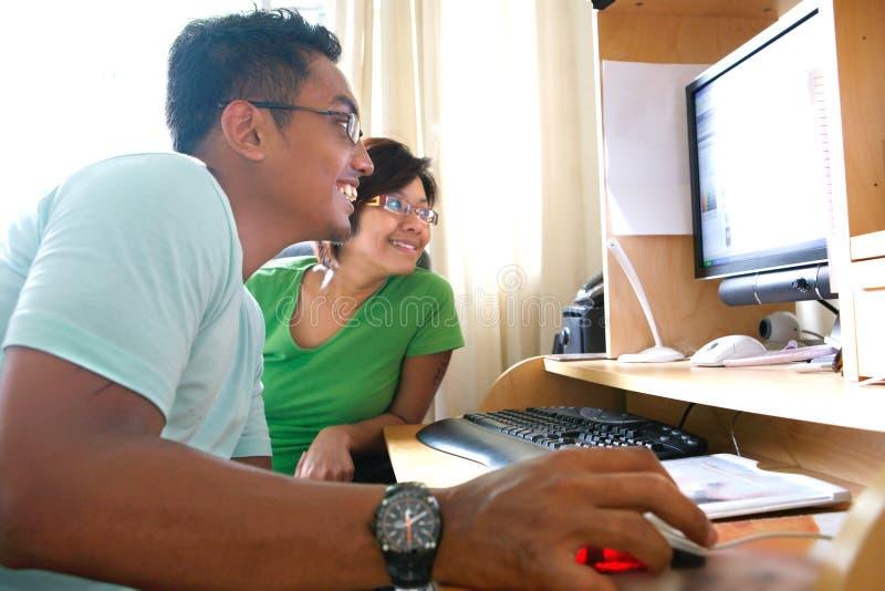 Coppie asiatiche che passano in rassegna il Internet immagine stock libera da diritti