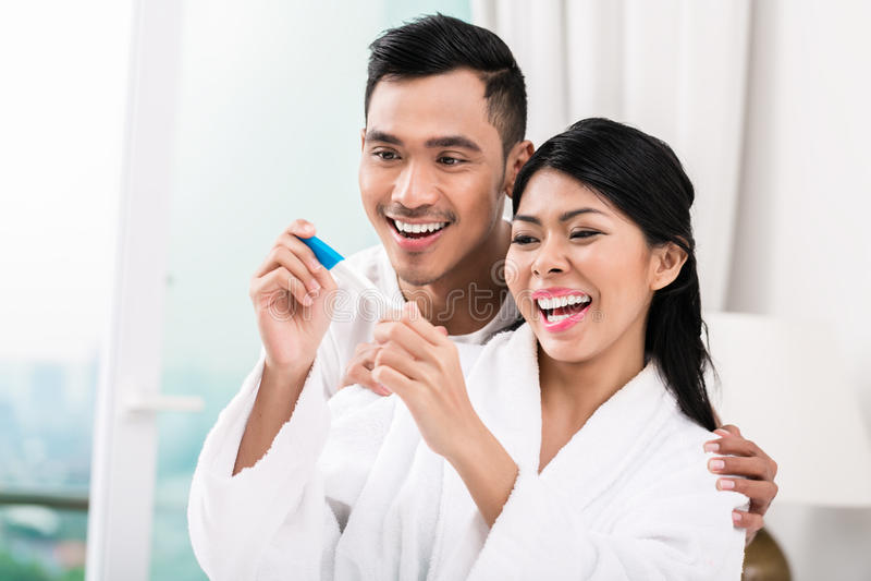 Coppie asiatiche con il test di gravidanza a letto immagine stock libera da diritti